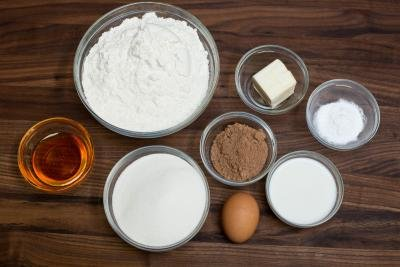 7 bowls on the table including one with flour, one with sugar, one with cocoa, one with milk, one with butter, one with baking soda and one with honey also an egg on the table