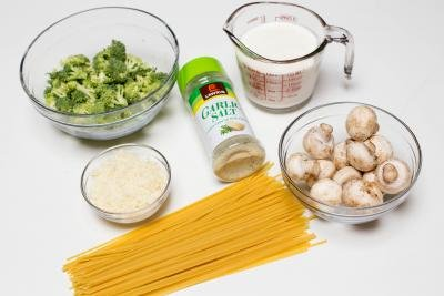 Ingredients on the table including; spaghetti, mushrooms in a bowl, broccoli in a bowl, parmesan in a bowl, whipping cream in a measuring cup and garlic salt