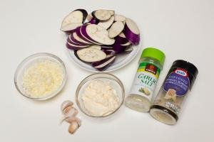 Eggplant cut in slices on a plate, mozzarella in a bowl, mayo in a bowl, garlic cloves, garlic salt and cheese