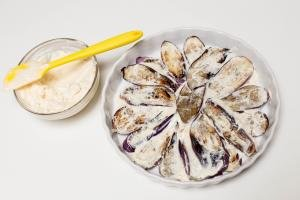 Eggplant slices layer out on a plate and garlic mayo spread on top of the eggplant