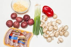 Ingredients on the table including; mushrooms, green onions, potatoes, red bell pepper, a bowl with cheese and Johnsonville Brats