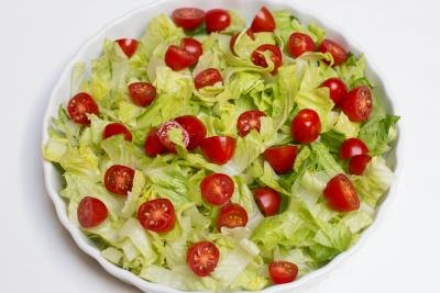 Halved tomatoes added into the serving tray with the cut up lettuce