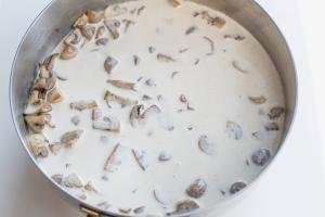 Mushrooms and heavy whipping cream in a deep skillet