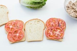 3 slices of bread, 2 with onions and tomatoes on them and one with nothing on it