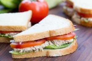 A half of a tuna sandwich on a cutting board