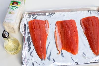 3 salmon fillets on a baking pan lined with foil with garlic salt and oil besides the pan