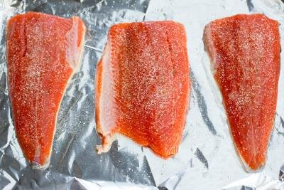 3 seasoned salmon fillets on a baking pan lined with foil
