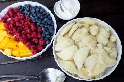 Vareniki in a bowl with another bowl of fruits on the side