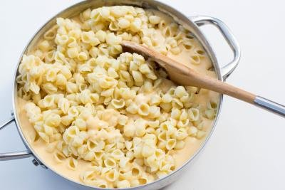 macaroni being mixed into the cheese mixture in the deep skillet