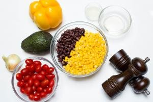 Ingredients on the table including; an onion, avocado, a yellow bell pepper, a bowl with baby tomatoes, a bowl with black beans and corn, salt and pepper, and 2 little bowls one with lemon juice and one with oil