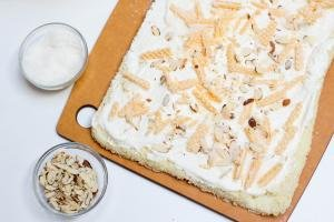 Wafers placed on top of the cream on the cake roll, with 2 little bowls besides the cake one with sliced almonds and one with coconut