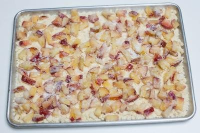 Plum mixture spread on top of the crumble batter in the baking pan