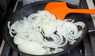 half ring onions being caramelized on a skillet