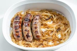 A ceramic baking pan filled with caramelized onions and Johnsonville Beer Bratwurst sausages placed on top