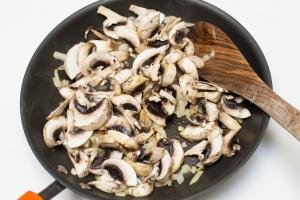 Mushrooms added into the skillet with the sautéing onions