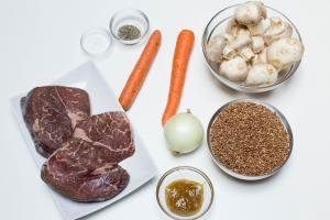 Ingredients on the table including; 2 carrots, an onion, buckwheat in a bowl, mushrooms in a bowl, beef on a plate, better than bouillon in a bowl, and 2 bowls with salt and pepper