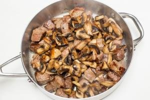 Beef and mushrooms in a deep skillet