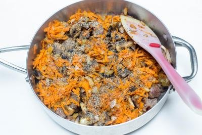Seasoning, carrots and onions, beef and mushrooms in a deep skillet