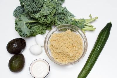 Ingredients on the table including; 2 avocados, a cucumber, 2 eggs, kale, a bowl of quinoa, a bowl of ranch