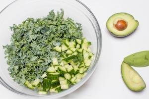 Chopped up kale and cucumber in a bowl with a halved avocado beside the bowl