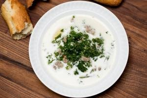 Zuppa Toscana Soup Recipe in a bowl on a cutting board with baguette pieces near the bowl