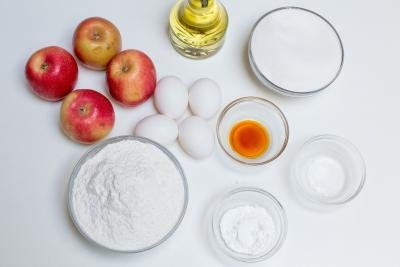 Ingredients on the table including; 4 apples, 4 eggs, oil, a bowl of sugar, bowl of flour, bowl of vanilla extract, bowl of baking powder and bowl of salt