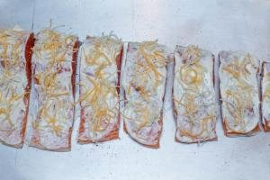 Mayo and cheese spread on salmon pieces on the baking pan