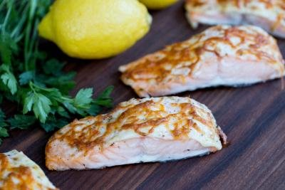 Baked Salmon on a cutting board with lemons besides the salmon