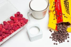 Ingredients on the table including; raspberries, chocolate chips, sugar, and a measuring cup of heavy whipping cream