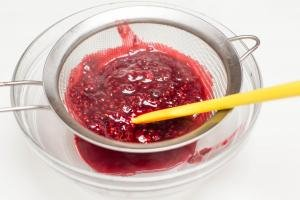 Raspberry mixture being strained through a strainer into a bowl