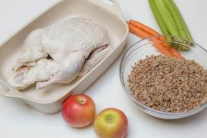 Seasoned duck in a ceramic baking pan, 2 apples, 2 carrots, celery, and buckwheat in a bowl