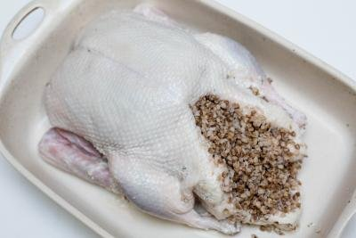 Seasoned duck in a ceramic baking pan filled with buckwheat