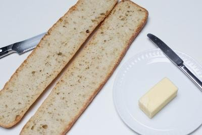 A baguette, cut in half the long way, a stick of butter with a butter knife besides the bread