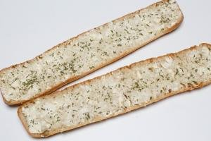 2 halves of a baguette with butter, garlic salt and parsley spread on it