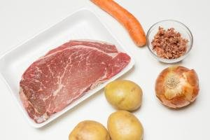 Ingredients on the table including; beef, 3 potatoes, an onion, a carrot and a little bowl of bacon