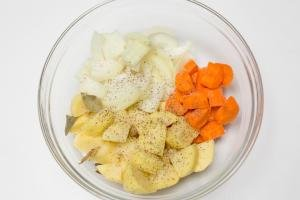 Cut up onions, carrot and potatoes, seasoned in a bowl