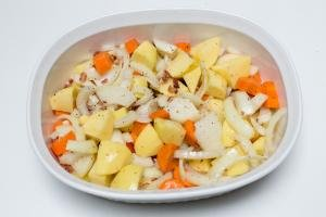 Seasoned veggies and bacon spread on the bottom of a ceramic baking dish