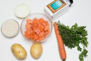 Ingredients on the table including; 2 potatoes, a carrot, rice in a bowl, salmon cut into cubes in a bowl, dill, parsley, half an onion and sea salt