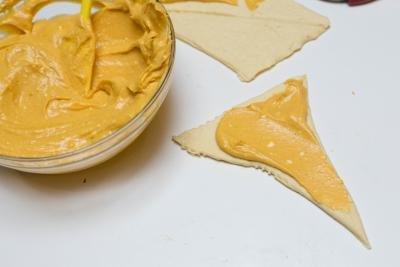 Pumpkin puree mixture being spread on a crescent dough piece