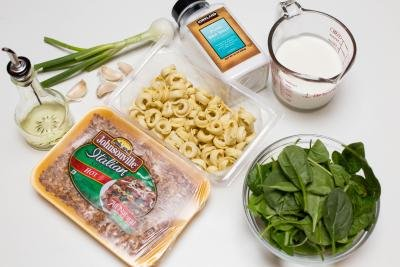Ingredients on the table including; Johnsonville Italian sausage, spinach in a bowl, tortellini, garlic cloves, green onion, oil, sea salt and a measuring cup with heavy whipping cream