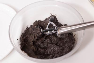 Oreo mixture being scooped out of a bowl with an ice cream scooper