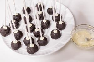 Cake pop stick being dipped into a bowl with white chocolate and then into the oreo balls on a plate