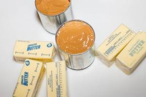 2 jars of dulce de leche and 5 sticks of butter on the table