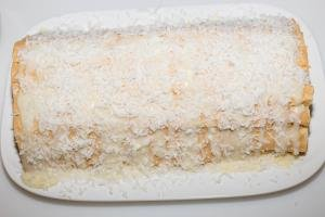 Coconut flakes being sprinkled on top of the Napoleon Log Cake
