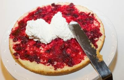 Cream being spread on a cake layer with the cranberry sauce