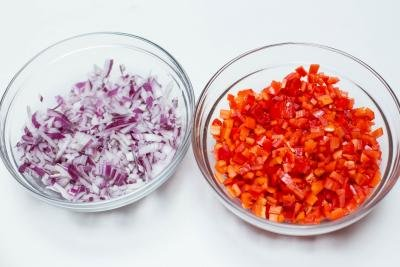 2 bowls one with diced purple onions and one with diced red peppers