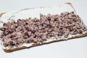 Drunken Cherry mixture being spread inside the unrolled cake