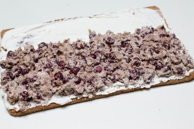 Drunken Cherry mixture being spread inside the unrolled cake