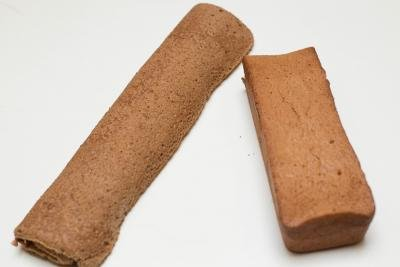 Cake roll on the table and a loaf made of the cake batter besides it