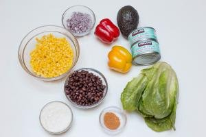 Ingredients on the table including; a bowl with corn, a bowl with beans, a bowl with diced purple onions, a bowl with ranch, a bowl with taco seasoning, lettuce, a red bell pepper, a yellow bell pepper, an avocado, and 2 cans of tuna